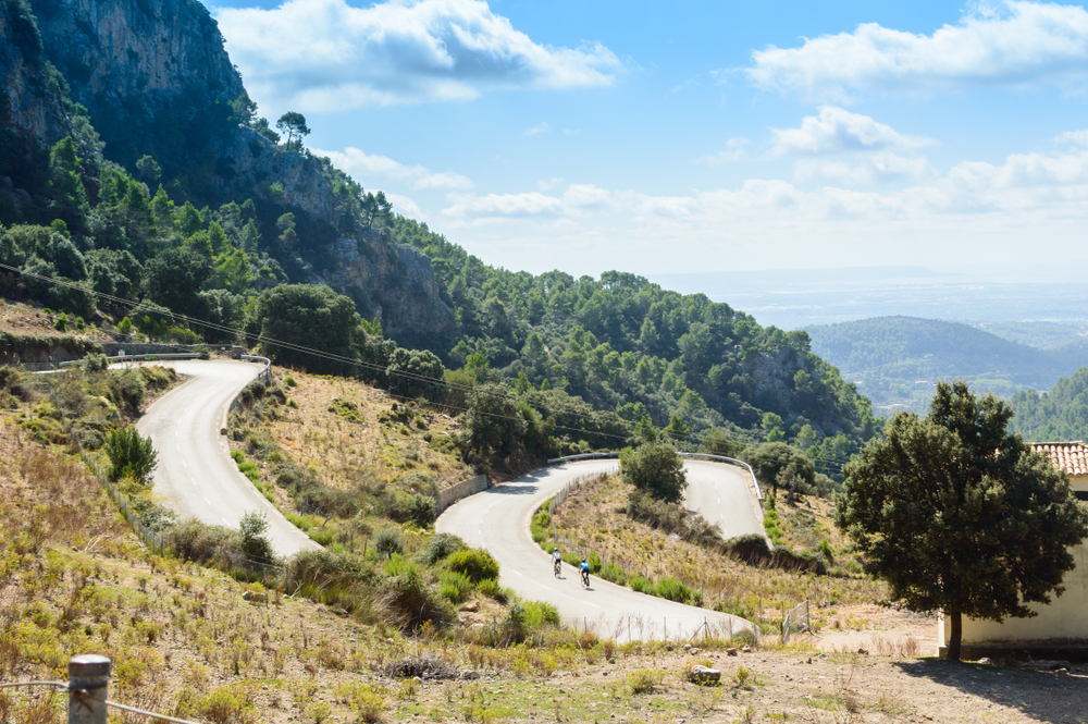 Cyclists cross the serpentine road of the Sierra of Tramontana, on the Island of Mallorca