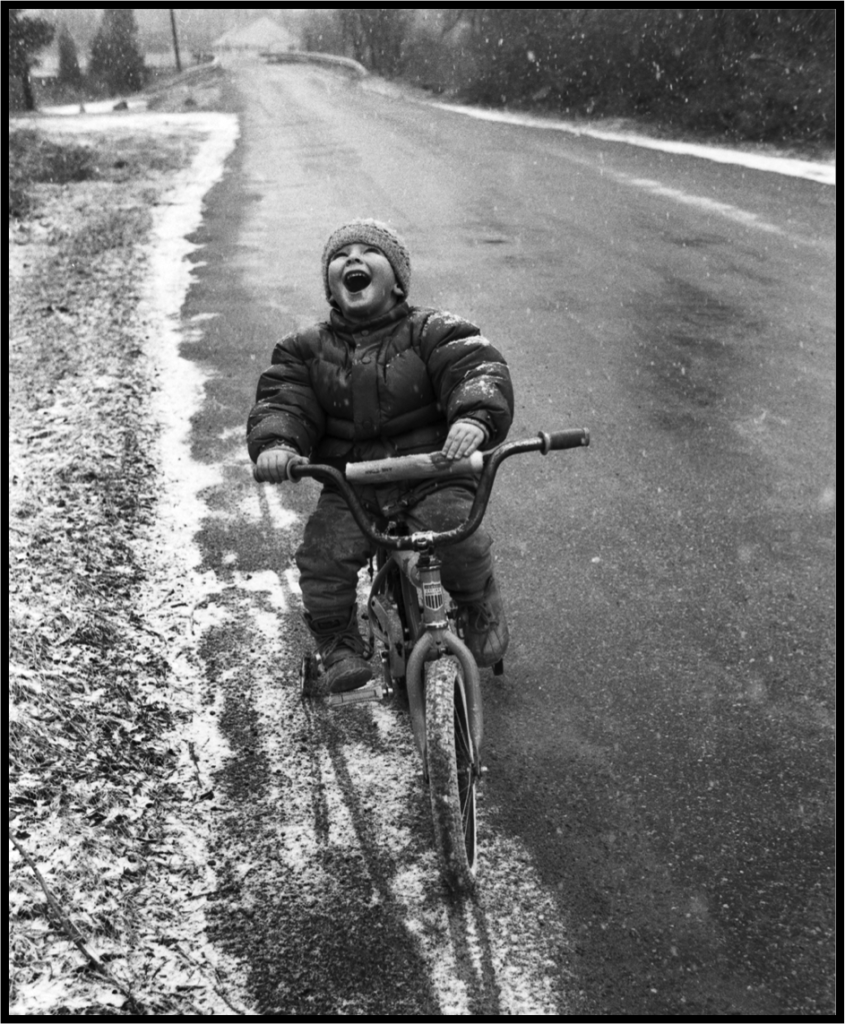 Boy riding a bike in the snow and laughing